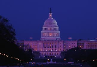 View of the exterior of the U.S. Capitol at night.